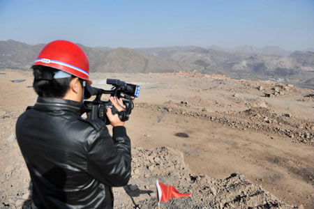 A reporter for Xinhua News Agency is filming the site where the explosion happened on October 15, 2009.